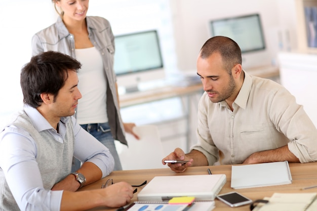 Pessoas no escritório usando smarphone enquanto aguarda reunião