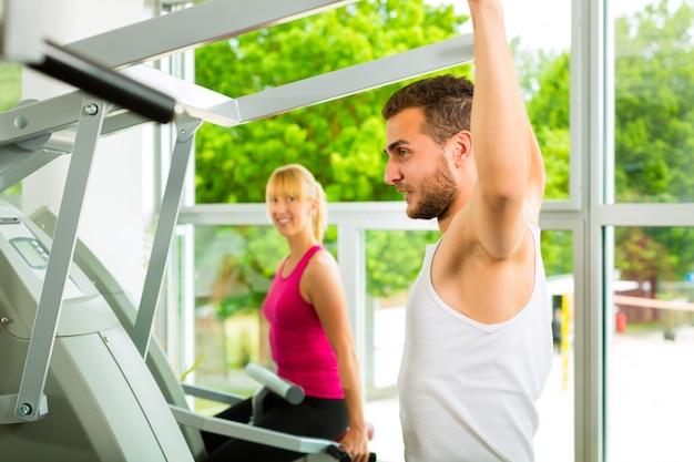 Pessoas no ginásio de esporte na máquina de fitness