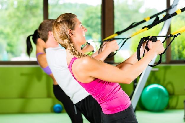 Pessoas no ginásio de esporte no instrutor de suspensão