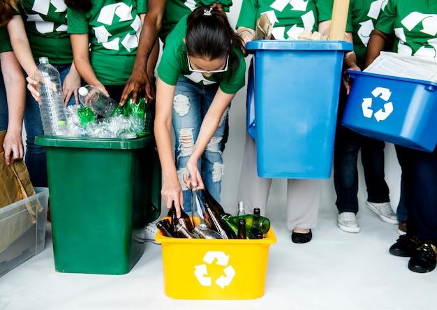 Pessoas no grupo ajudando juntos para colocar garrafas para reciclagem
