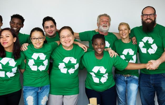 Pessoas no grupo vestindo camisas de ícone de reciclagem e posando para photoshoot