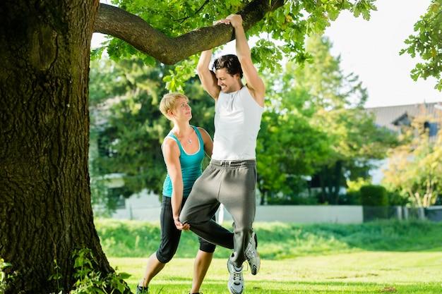 Pessoas no parque da cidade fazendo o queixo ou puxe ups na árvore