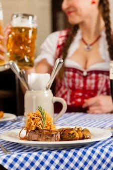 Pessoas no tradicional tracht da baviera comendo no restaurante ou pub