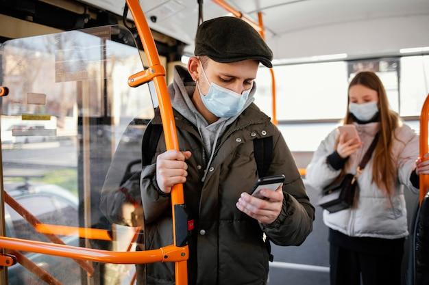 Pessoas no transporte público usando máscara