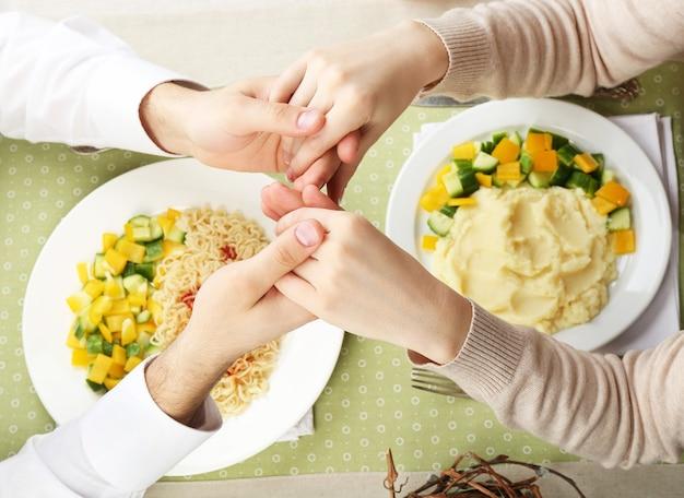 Pessoas orando antes de comer, vista de cima