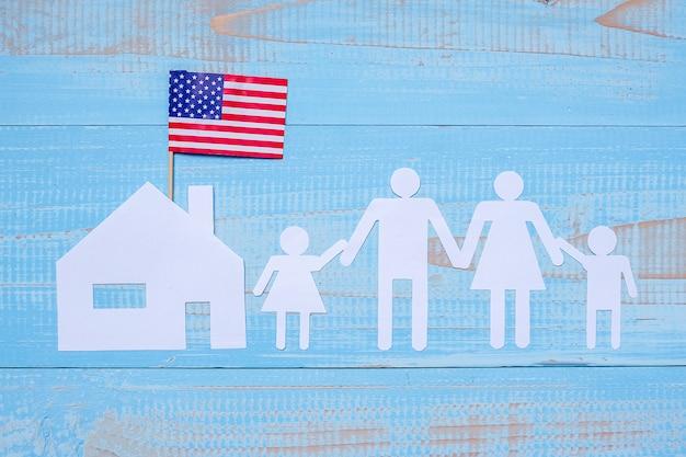 Pessoas ou família e forma de papel para casa com a bandeira dos estados unidos da américa
