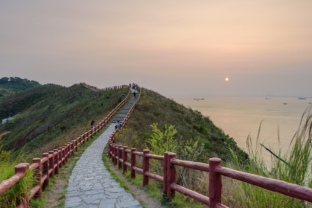 Pessoas passando por uma rota estreita com uma cerca vermelha durante o pôr do sol