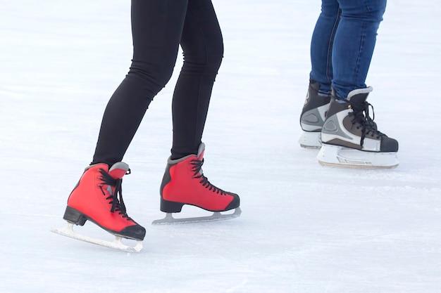 Pessoas patinando no gelo em uma pista de gelo. hobbies e esportes. férias e atividades de inverno.