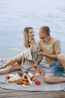 Pessoas perto do rio. piquenique delicioso de verão saudável na grama. frutas em uma blancet.