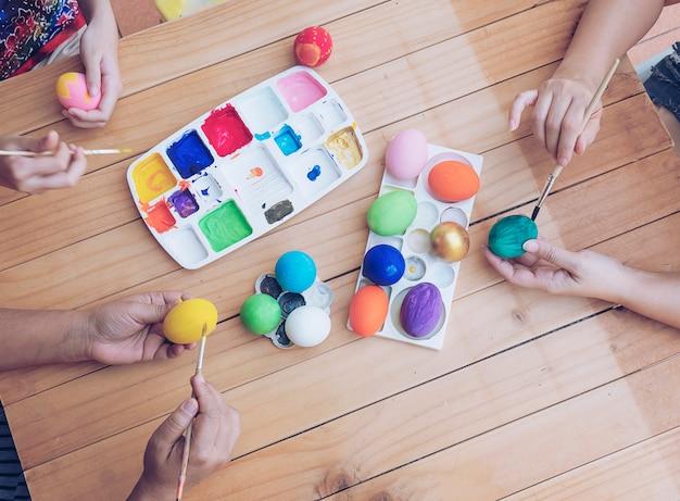 Pessoas pintar ovos de páscoa coloridos - conceito de celebração de feriado de páscoa