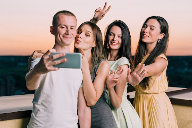Pessoas posando para selfie no telhado ao amanhecer