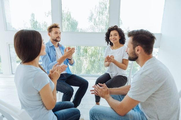 Pessoas positivamente agradáveis e encantadas sentadas em círculo e aplaudindo umas às outras durante uma sessão de terapia psicológica