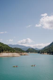 Pessoas praticando esporte (caiaque) em um dia ensolarado em um lago de água azul, rodeado por montanhas no verão