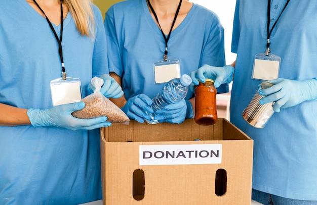 Pessoas preparando caixa com comida para doação