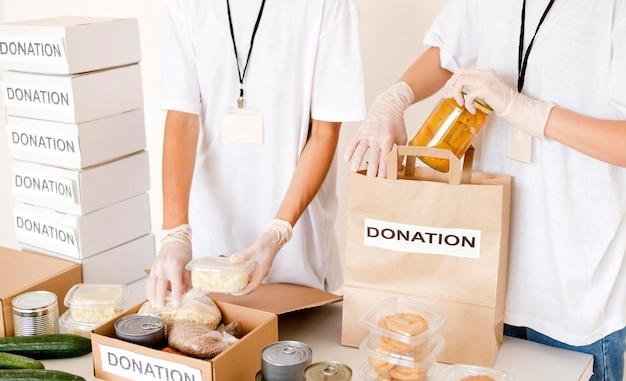 Pessoas preparando comida caixa e bolsa para doação
