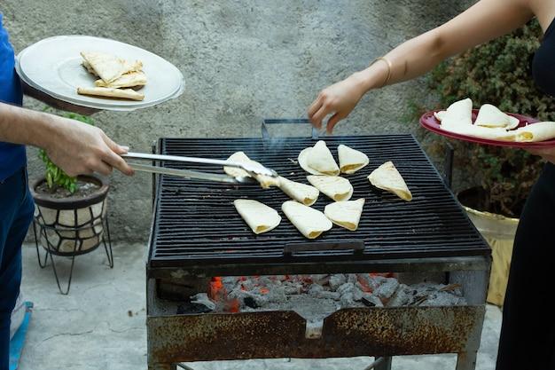 Pessoas preparando quesadillas em uma grelha a carvão
