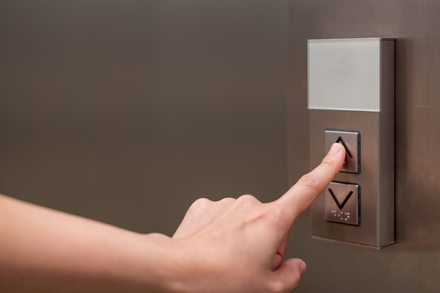 Pessoas pressionando o botão no elevador e selecione o primeiro andar usando o dedo indicador.