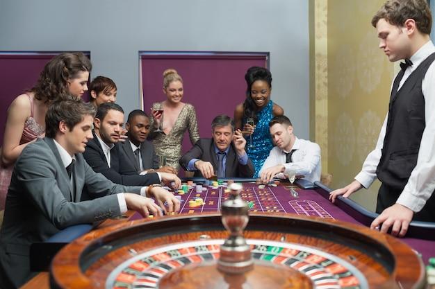 Pessoas que colocam apostas na mesa de roleta