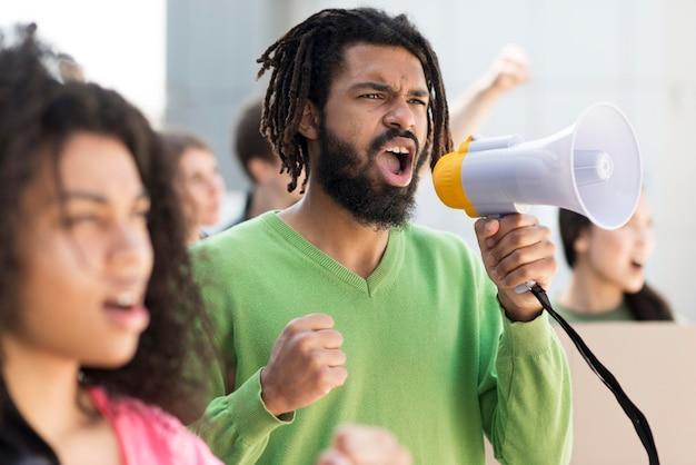 Pessoas que protestam nas ruas com megafones