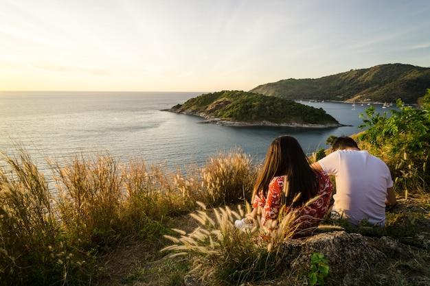 Pessoas que se amam e são um casal sentados juntos em uma colina e tem vista para