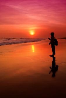 Pessoas que texting durante o pôr do sol na praia de parangtritis, yogyakarta.