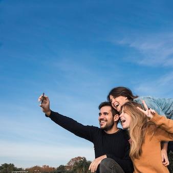 Pessoas que tomam selfie no fundo do céu azul