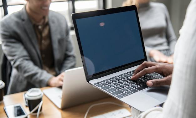 Pessoas que trabalham em um laptop em uma reunião