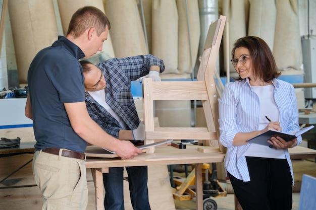Pessoas que trabalham em uma oficina de carpintaria, mulheres e homens fazendo amostras de cadeiras de madeira usando desenho de projeto