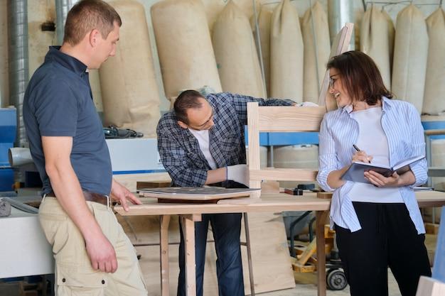 Pessoas que trabalham na oficina de carpintaria, mulheres e homens fazendo amostras de cadeiras de madeira usando desenho