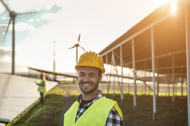 Pessoas que trabalham para painéis solares e turbinas eólicas - conceito de energia renovável - foco no rosto do homem