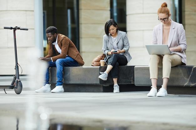 Pessoas que usam dispositivos móveis ao ar livre