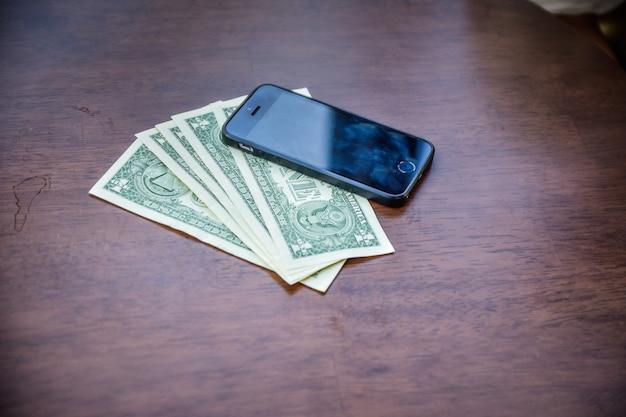 Pessoas que usam o smartphone para fazer compras on-line pela internet, smartphone e dólar americano em madeira para fazer compras ou economizar e investir
