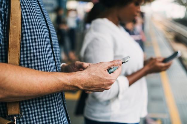 Pessoas que usam smartphones em uma plataforma de trem