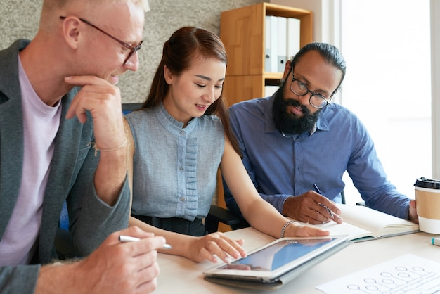 Pessoas que usam tablet digital no trabalho