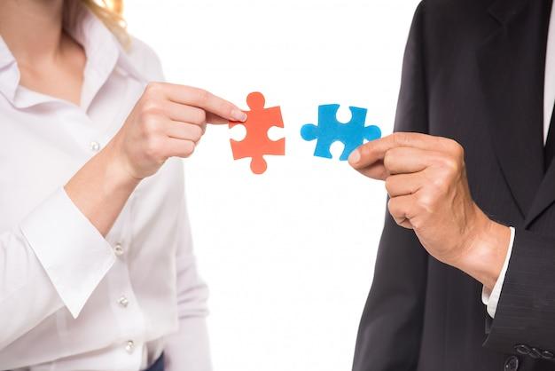 Pessoas querendo juntar duas peças de quebra-cabeça.