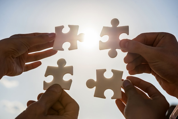Pessoas querendo juntar quatro peças de quebra-cabeça.