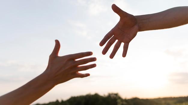 Pessoas querendo segurar as mãos umas das outras