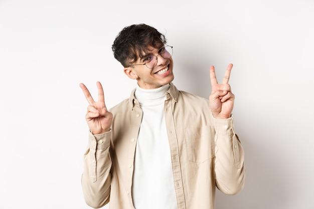 Pessoas reais. cara de hipster bonito em copos, mostrando gestos de paz e sorrindo fofo, de pé sobre um fundo branco.