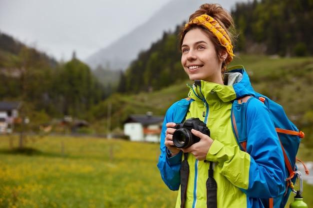 Pessoas, recreação, fotografando. viajante satisfeito segura câmera, mochila, sorri positivamente