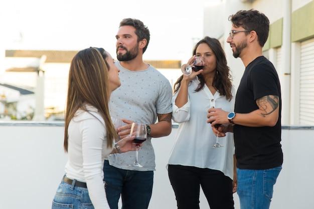 Pessoas relaxadas, bebendo vinho e conversando