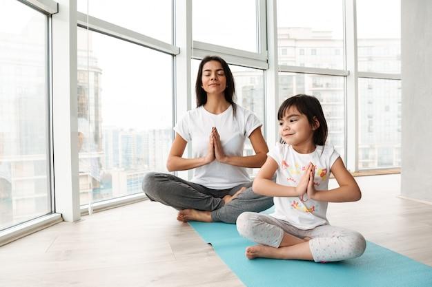 Pessoas relaxadas mulher e criança praticando ioga interior, sentado de pernas cruzadas na esteira e mantendo as palmas das mãos juntas