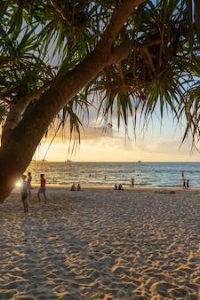 Pessoas relaxando e jogando vôlei na praia.
