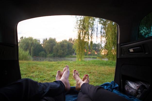 Pessoas relaxando no porta-malas de um carro perto de um lago