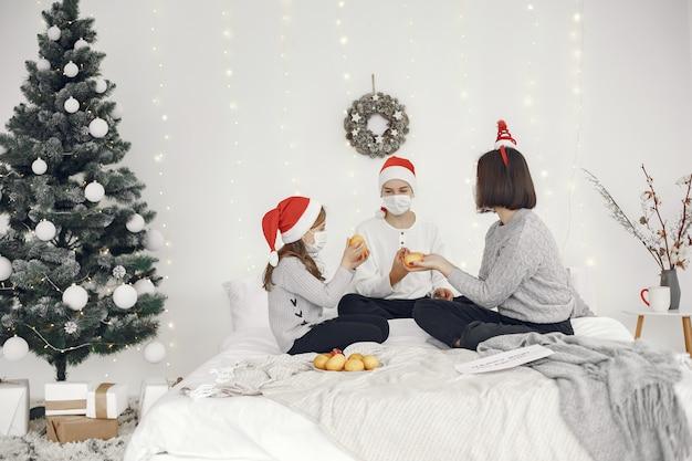 Pessoas reparando pelo natal. duas mães brincando com seus filhos. coronavirus thime. isolamento.