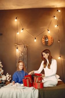 Pessoas reparando pelo natal. mãe brincando com sua filha. família está descansando em uma sala festiva. criança com um suéter azul.