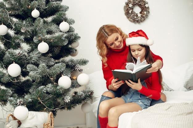 Pessoas reparando pelo natal. mãe brincando com sua filha. família está descansando em uma sala festiva. criança com um suéter vermelho.