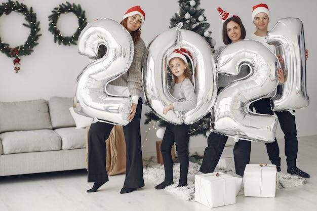 Pessoas reparando pelo natal. pessoas com balões 2021 / família descansando em uma sala festiva.