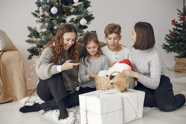 Pessoas reparando pelo natal. pessoas sentadas perto da árvore de natal.