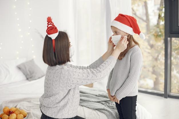 Pessoas reparando pelo natal. tema coronavirus. mãe brincando com sua filha. criança com um suéter cinza.