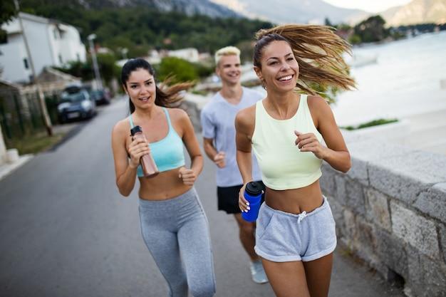 Pessoas saudáveis e em forma correndo e correndo juntas na natureza ensolarada do verão